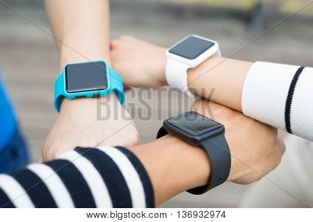 Athlete comparing time on smart watch with friend