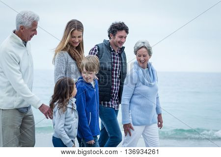 Happy family walking at beach against sky