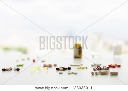 Closeup of white table with colorful pills and capsules blurry medicine bottles and a glass of water. Selective focus