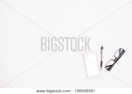 Top view of white desktop with blank cellphone glasses and pen. Mock up