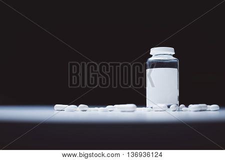 Closeup of white pills and prescription bottle in the spotlight