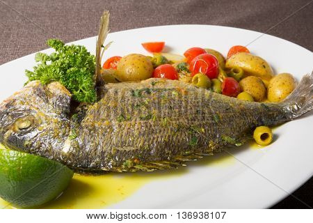 Grilled dorado fish served with potato garnish