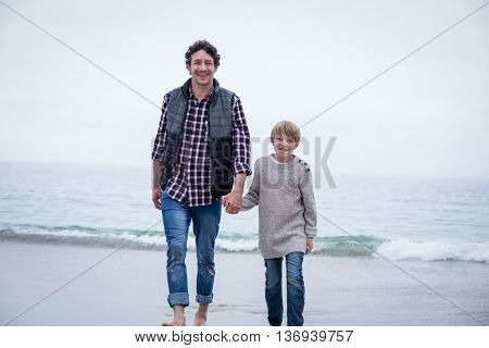 Portrait of happy father and son walking at sea shore against sky