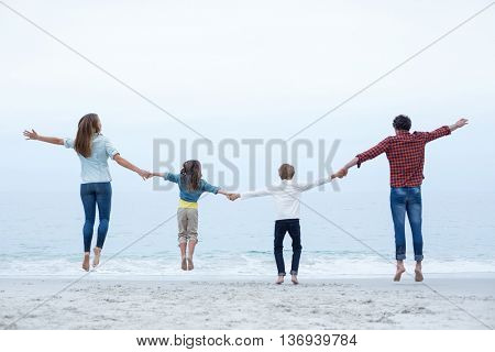 Rear view of family holding hands while jumping at sea shore against sky