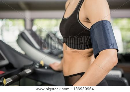 Happy woman with mobile on armband at gym