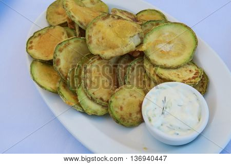 Fried zucchini chips with tzatziki Greek tavern plate. Floured zucchini are a dish commonly served at Greek tavernas, with a tzatziki sauce made of yogurt, cucumbers, salt, olive oil, and vinegar.