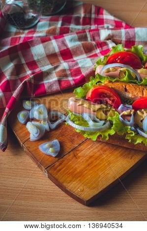 Hotdogs with fresh salad and tomatoes on wooden cutting Board