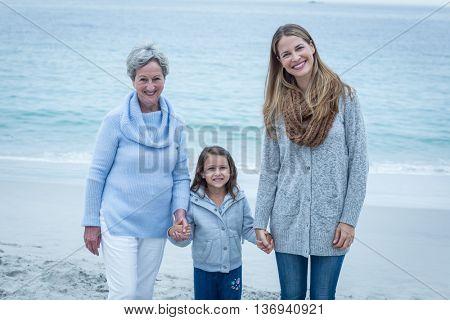 Portrait of three generations of women standing at beach