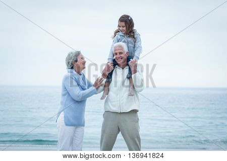 Happy grandparents with granddaughter enjoying at beach
