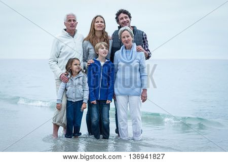 Smiling family looking away while standing at beach against sky