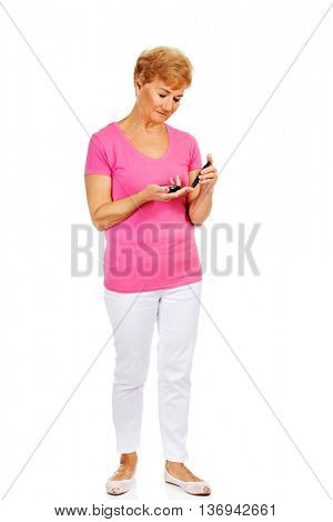 Senior woman with glucometer checking blood sugar level