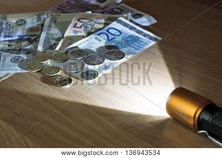 In a dark room a beam of light of the electric lantern lights money lying on the table.