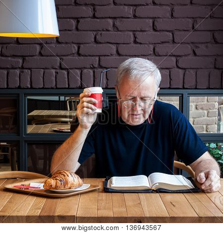 Man sitting at a table with a coffee and a croissant in a snack bar and reading the Bible. Working break dedicated to material and spiritual feeding.