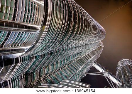 KUALA LUMPUR MALAYSIA - FEBRUARY 29: Bottom view of Petronas twin towers at night on February 29 2016 in Kuala Lumpur Malaysia. Night scene of famous skyscraper.