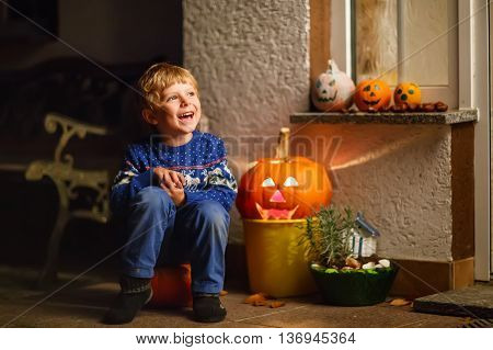 Little kid boy sitting with traditional jack-o-lanterns pumpkins for halloween by the decorated scary door, outdoors. Child having fun and celebrating holiday.