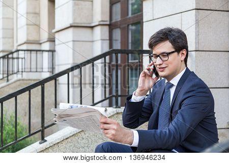 Businessman On Phone Reading Newspaper