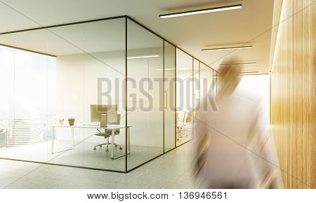 Side view of blurry businessman walking in office interior with blank whiteboard behind glass doors and hallway with wooden wall New York city view and sunlight. Mock up 3D Rendering