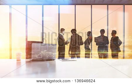 Businesspeople silhouettes working in office with large table laptop coffee cup and paperwork on city background. Double exposure. Concept of teamwork