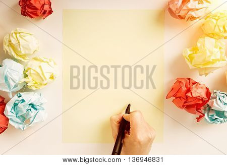 Hand drawing something on blank paper sheet surrounded with colorful crumpled paper balls. Mock up