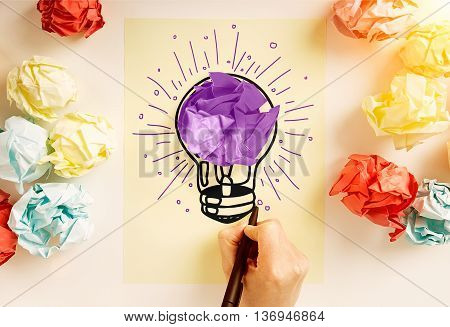 Creative idea concept with hand drawing abstract purple lightbulb sketch on paper sheet surrounded with colorful crumpled paper balls