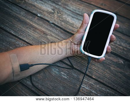 an arm with a cell phone hooked intravenously with the charger cord and a bandaid covering the end tip - social media addiction concept toned with a retro vintage instagram filter app or action effect