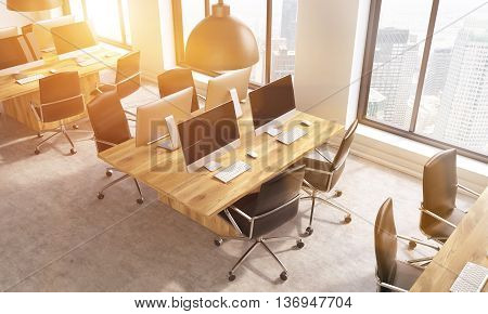 Coworking office interior with multiple blank computer screens on workplaces and windows with New York city view. View from above. Toned image 3D Rendering