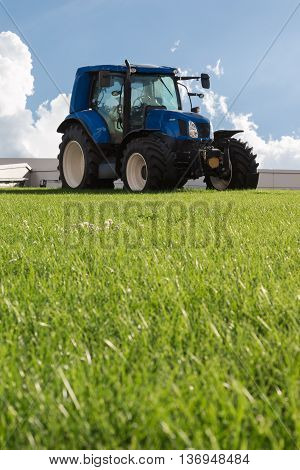 Blue Brilliant Agricultural Tractor on Green Declivity Field