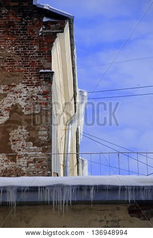 Roof with drain. Peeling winter wall with icicles