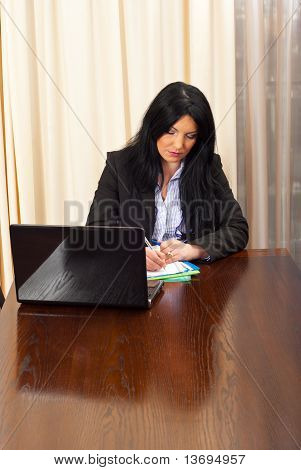 Serious Business Woman Writing In Office