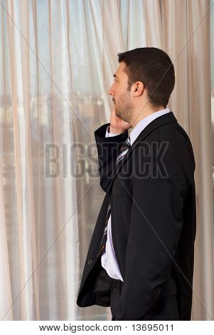 Business Man On Cellphone Look Through Window
