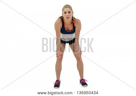 Tired athlete standing with hand on knee on white background