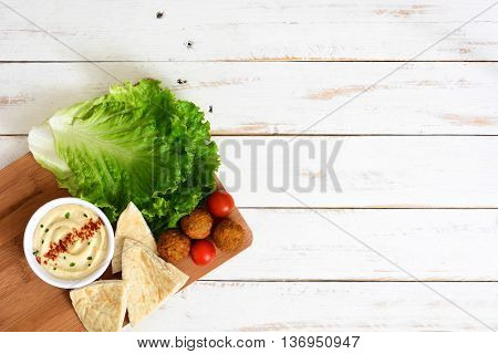Vegetarian falafels and hummus on a white wooden background