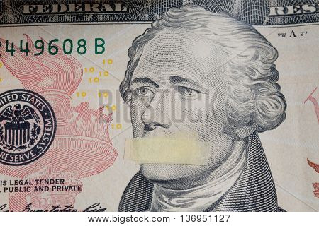 Portrait of the American president Alexander Hamilton with mouth closed on the banknote of ten dollars USA as a symbol of the instability of the economy system