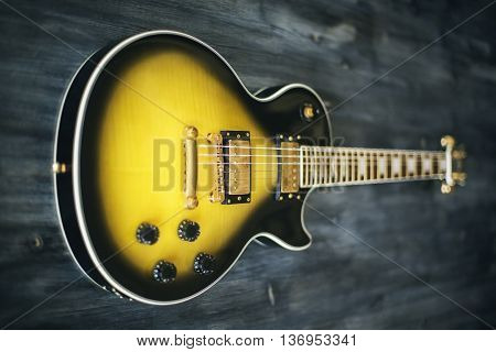 Closeup of black and yellow electric guitar on wooden surface