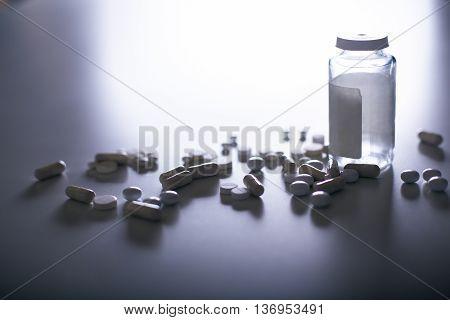 White pills and capsules next to prescription bottle in the spotlight
