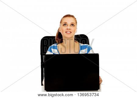 Teenage woman with laptop looking up