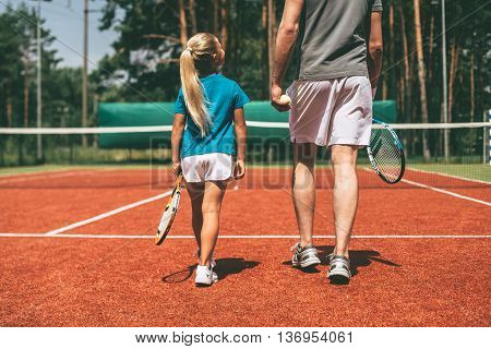 Preparing to big game. Rear view of little blond hair girl in sports clothing carrying tennis racket and looking at her father walking near her by tennis court