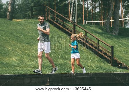 Jogging with father. Full length of cheerful father and daughter jogging in park together