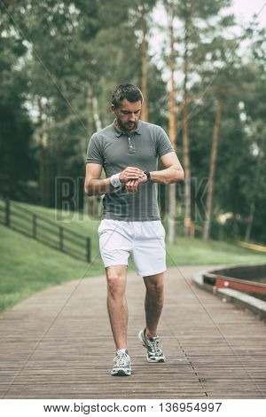 New great result! Full length of confident man in sports clothing looking at his wristwatch while walking in park