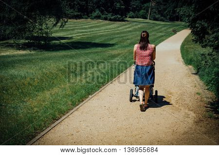 Mother with baby carriage walking in path on park. Retro stylized photo. Mother with baby carriage walking in path on park. Retro stylized photo. View from behind.