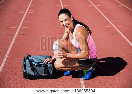 Portrait of happy female athlete with her sports accessories on running track
