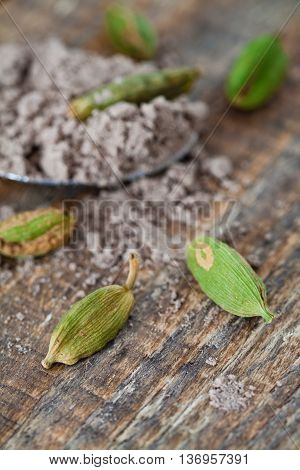 Tablespoon of ground cardamom and pods on wooden table.