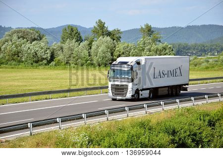 Dolny Hricov, Slovakia - June 29, 2016: White moving Volvo truck coupled with semi-trailer located on slovak D1 highway.