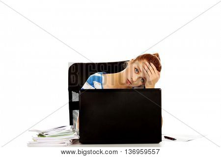 Tired teen woman with laptop sitting behind the desk
