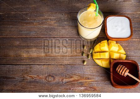Top view of glass milkshake with mango yoghurt and honey with copy space on wooden board.