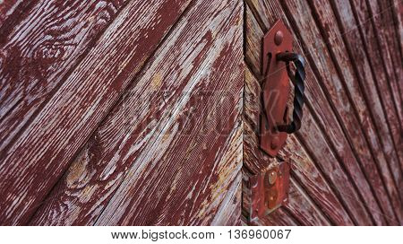 part of the old wooden gate collapsing under the influence of weather conditions, red and brown shades, a metal hand and the lock