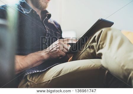 Bank account manager reading business news modern Interior Design Loft Office.Man relax Vintage Sofa, Use contemporary tablet, share information.Blurred Background.New Startup Idea Process.Closeup