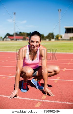Portrait of happy female athlete warming up on running track