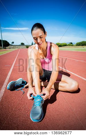 Happy female athlete tying her running shoes on running track