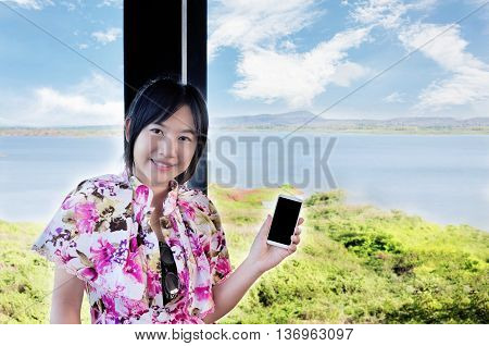 Asian Women Smiling Presenting Smartphone Or Cellphone In Hand